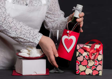 Deliver Holding Wine Bottle with red Heart of Valentine's Day near festive bag and white box for cakes