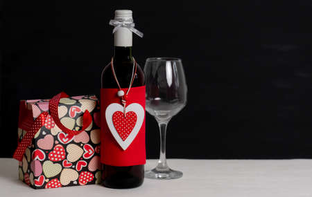 Wine Bottle, Shopping bag, white box and red Heart of Valentine's Day on the black background