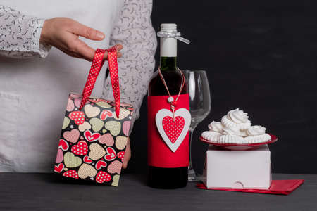 Deliver Holding Festive Bag near Wine Bottle with red Heart of Valentine's Day and cakes Banco de Imagens