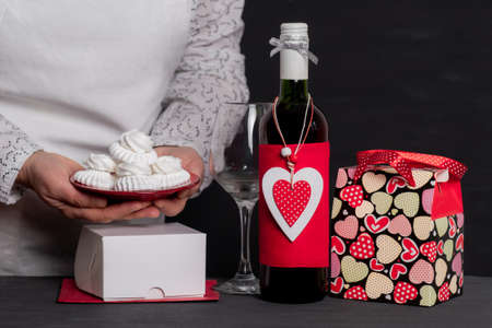 Deliver Holding cakes near Wine Bottle with red Heart of Valentine's Day and festive bag Banco de Imagens