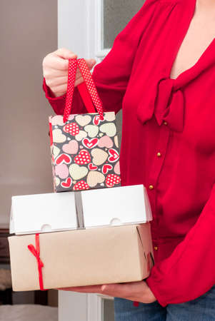 Woman's hands holding Shopping bag with red Hearts of Valentine's Day and Gifts Boxes near the white door.