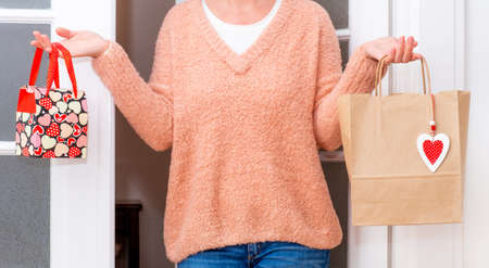 Woman's hands holding Shopping bags with red Hearts of Valentine's Day near the white door.