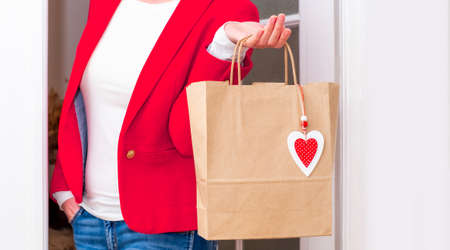 Woman's hands holding Shopping bag with red Hearts of Valentine's Day near the white door.