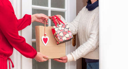 Woman's hands Delivering Shopping bag with Red Hearts of Valentine's Day and Gifts Boxes from Worker of Delivery Service. Banco de Imagens