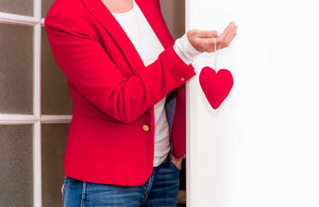 Woman's hand holding red big Heart of Valentine's Day near the white door. Banco de Imagens - 161048292