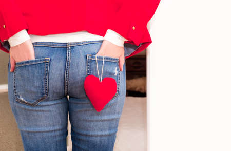 Woman's hands in the back pockets of jeans with red big Heart of Valentine's Day near the white door. Banco de Imagens - 161048296