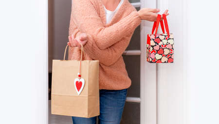 Woman's hands holding Shopping bags with red Hearts of Valentine's Day near the white door. Banco de Imagens - 161048298