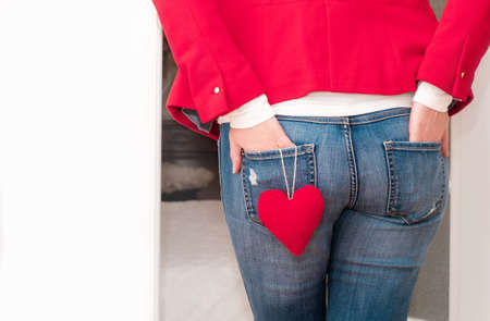 Woman's hands in the back pockets of jeans with red big Heart of Valentine's Day near the white door.