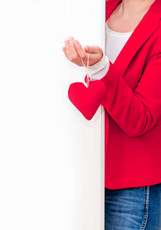 Woman's hand holding red big Heart of Valentine's Day near the white door.
