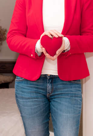 Woman's hands holding red big Heart of Valentine's Day near the white door. Banco de Imagens