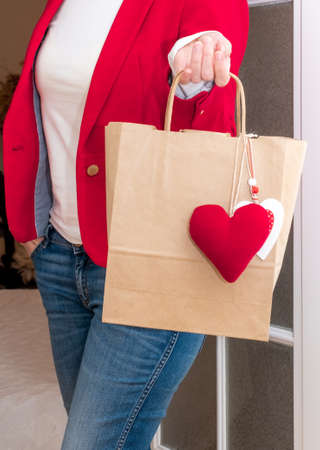 Woman's hand holding Shopping bag with red Hearts of Valentine's Day.