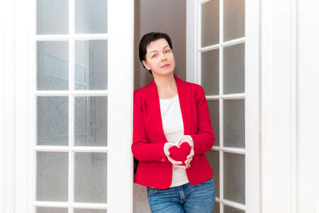 Middle Aged Woman holding in her hands red big Heart of Valentine's Day near the white door. Banco de Imagens - 161048316