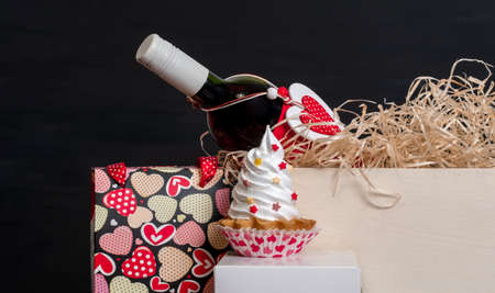Wine bottle, shopping bag with hearts and meringue cake on the black background for Valentine's day.