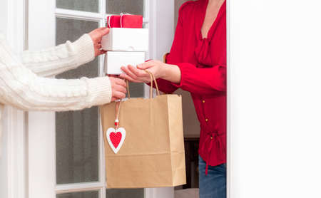 Woman's hands Delivering Shopping bag with Red Hearts of Valentine's Day and Gifts Boxes from Worker of Delivery Service. Banco de Imagens - 161171181