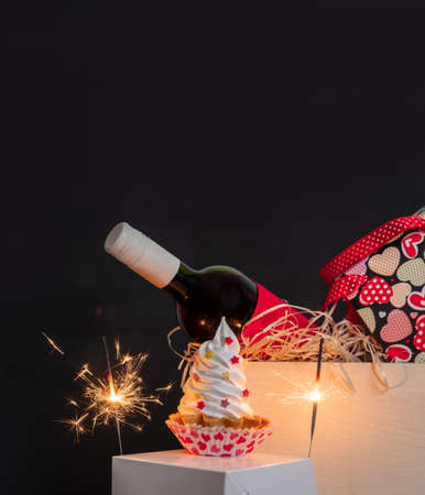 Sparkler, wine bottle, shopping bag with hearts and meringue cake on the black background for Valentine's day. Banco de Imagens - 161171182