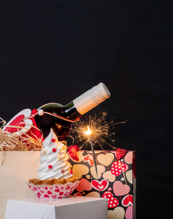 Sparkler, wine bottle, shopping bag with hearts and meringue cake on the black background for Valentine's day. Banco de Imagens
