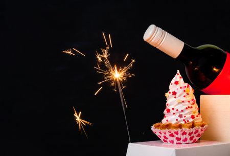 Sparkler, wine bottle, and meringue cake on the black background for Valentine's day.