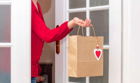 Woman's hands holding Shopping bag with red Hearts of Valentine's Day near the white door. Banco de Imagens - 161171185