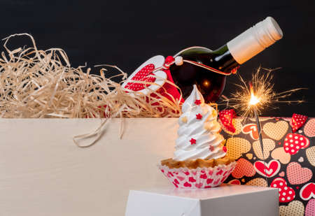 Sparkler, wine bottle, shopping bag with hearts and meringue cake on the black background for Valentine's day. Banco de Imagens - 161171190