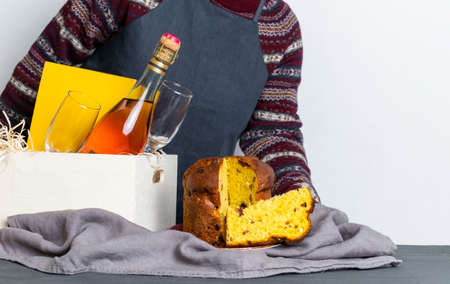 Female hand holding easter panetone italian piece near delivery box with champagne bottle. Banco de Imagens