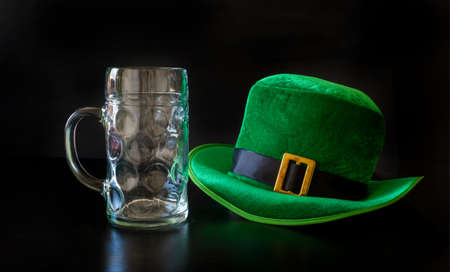 A St. Patrick's day hat of a leprechaun and glas of beer on the black background