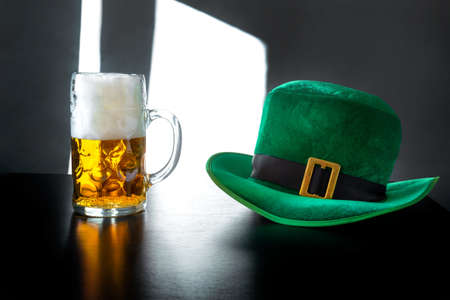 St. Patrick's day hat of a leprechaun and glass of beer on the gray background Banco de Imagens