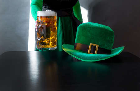 Woman's hand holding glass of beer near St. Patrick's day hat of a leprechaun on the black background Banco de Imagens