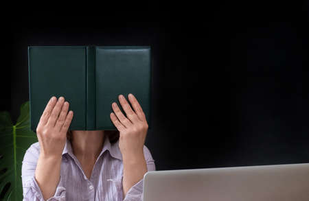 Woman closed your face of book near her workplace with laptop