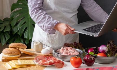 Female Chef cooking Big Burger or Cheeseburger and Using Laptop with Cooking Recipe Tutorial. Banco de Imagens