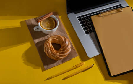 Hands Holding resume Sheet near Laptop, cake and cup of tea on the Fortuna Gold Yellow Color Background, top view.