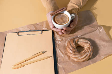 Hands Holding cup of tea or Mulled Wine near Resume Sheet and Cake on the Set Sail Champagne Color Background, top view.
