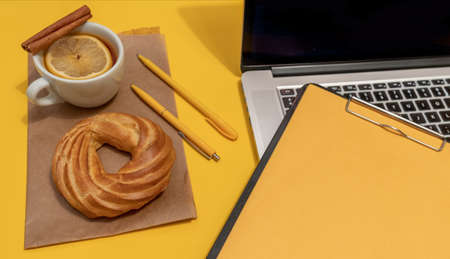 Laptop, cake, cup of tea and resume sheet on the Fortuna Gold Yellow Color Background, top view. Banco de Imagens
