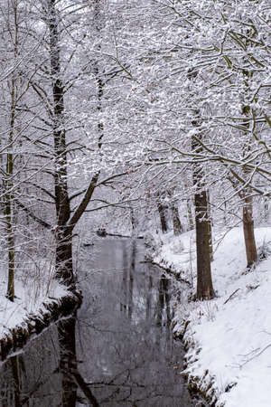 Winter scenery with snow, river or stream in the forest.