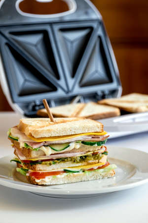 Fresh sandwich with cheese, herbs, tomato, cucumber and bacon on the toaster background Banco de Imagens