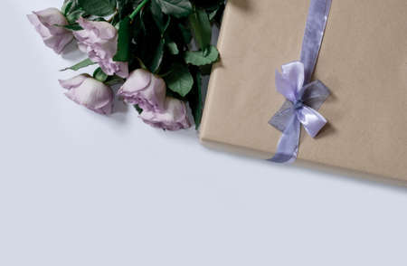 Bouquet from violet roses with gift box on the white background, top view, copy space. Banco de Imagens