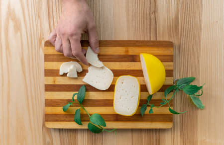 Hand takes Slices of Holland cheese Edam and dutch goat cheese from Netherlands, top view. Banco de Imagens