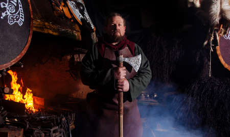 Viking forges weapons and swords in the smithy. A man in a warrior's clothes is in the smithy on the background of fire.