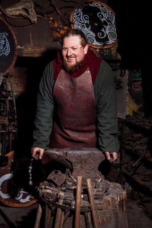 Viking forges weapons and swords in the smithy. A man in a warrior's clothes is in the smithy Banco de Imagens