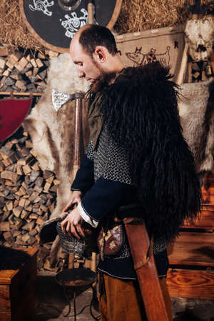 Viking posing against the background of the ancient interior of the Vikings.