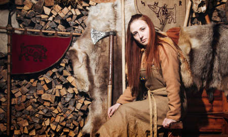 Vikings woman posing against the background of the ancient interior of the Vikings.