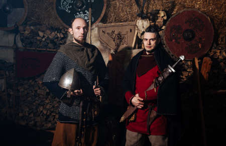 Vikings posing against the background of the ancient interior of the Vikings. Banco de Imagens