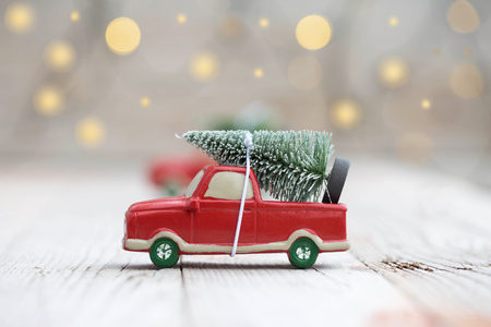 Miniature red car with fir tree on wooden background. Shallow DOF Stock Photo