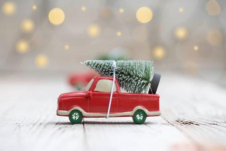 Miniatuur rode auto met fir tree op houten achtergrond. Ondiepe DOF