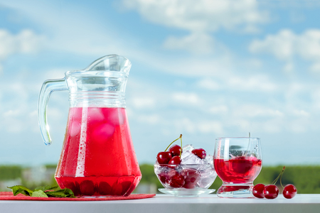 Fresh cool drink from a cherry. Cherries on ice. Summer still life against the sky.