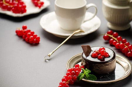 milkman: Chocolate cake with a red currant on a dish, cup and milkman