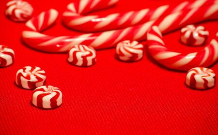 sugarplum: White and red candy caramel are on the table on the red burlap Stock Photo
