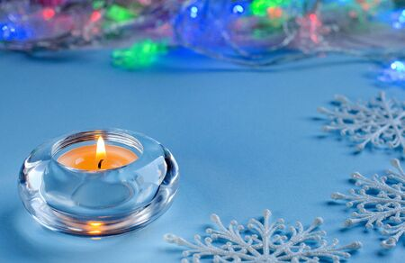 A small candle in a round glass candleholder. Flashing lights electric gasdandy. Blue background. Decorative white snowflakes. The Christmas cheer. Stock Photo