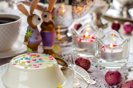 Panna cotta close up. Easter decor and beautifully decorated table for the occasion. Painted eggs. Figurines of bunnies. Silverware. Selective focus. Stock Photo