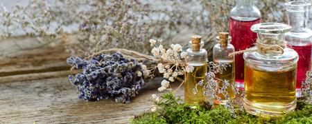 Bos van droge lavendel.Glasflessen aroma etherische oliën of Spa of natuurlijke aromatische olie op de oude planken met mos, Spa of alternatieve meditatie geur. Selectieve aandacht. Plaats voor tekst.