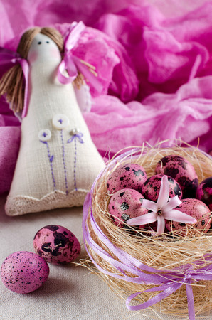 Decorative nest. Pink quail eggs. Easter background. Decorative toy. Girl-angel. Pink runner. Selective focus. Place for text.